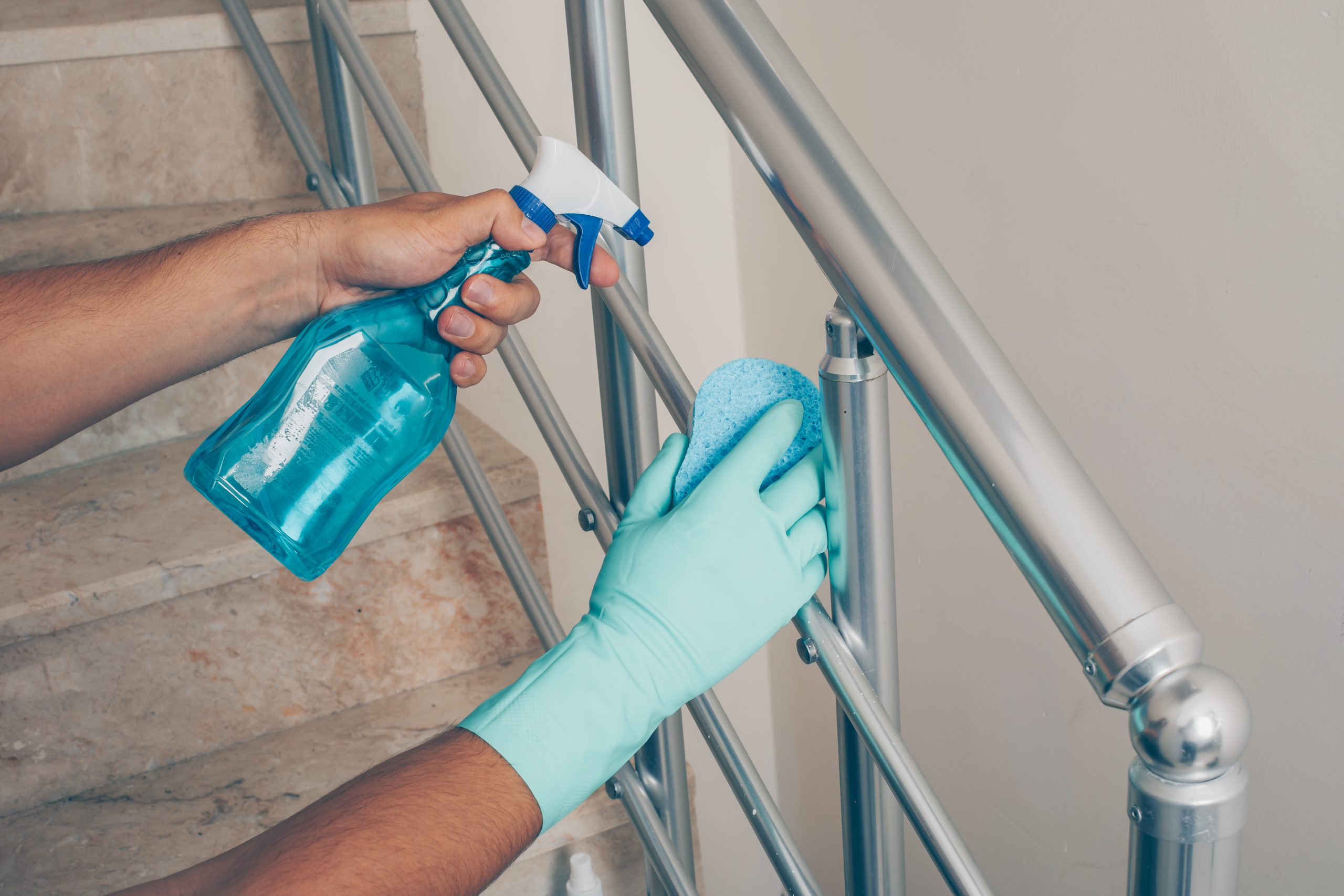 A man cleaning staircase handrail in gloves . coronavirus